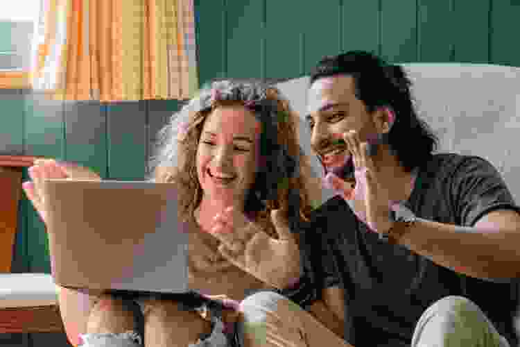 young couple waving to laptop screen during video call