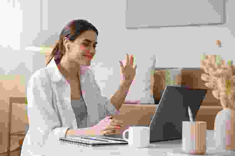 woman waving to coworkers on zoom during a happy hour