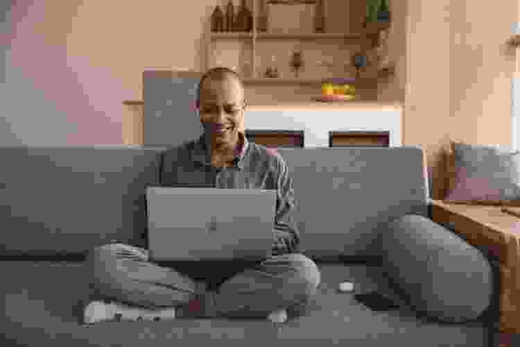 man with laptop joining a virtual netflix party on the couch