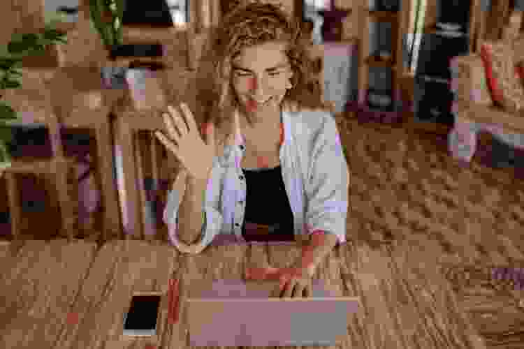 remote worker waving at team members through video chat