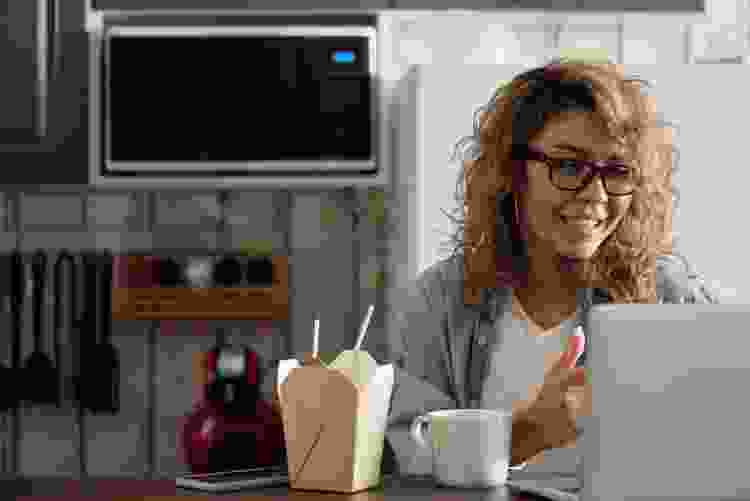 woman with takeout using laptop to play virtual games with remote teammates