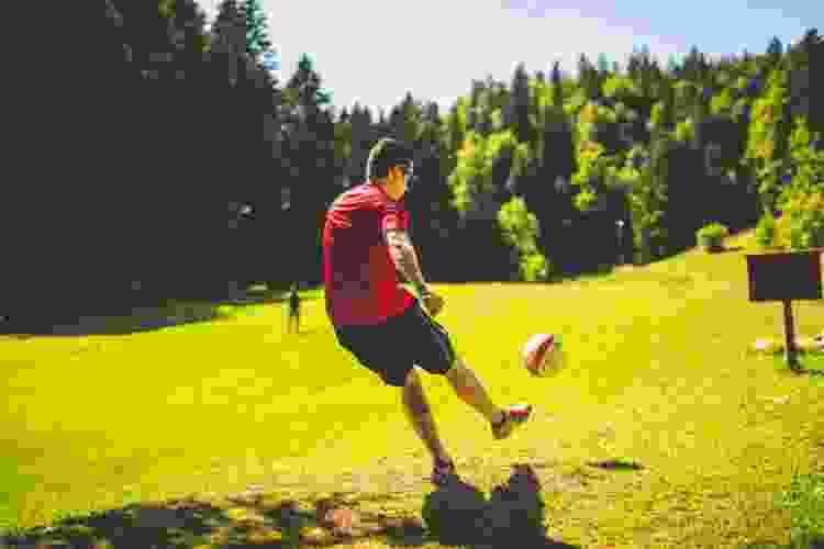 kicking a ball while playing a team building activity