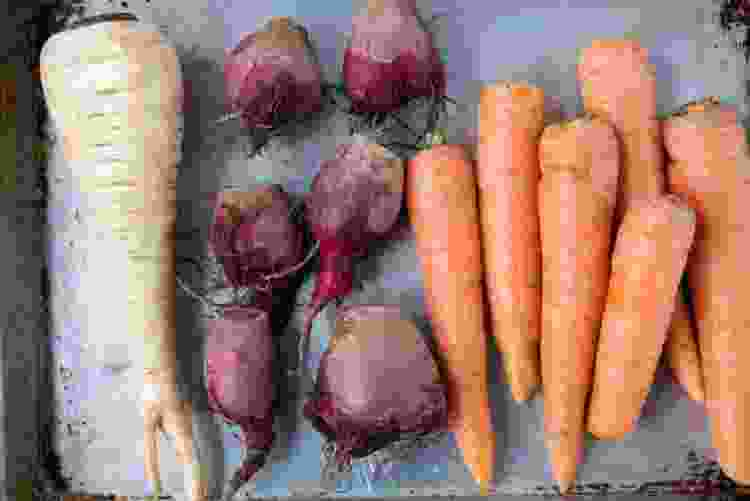 parsnips, beets and carrots on a baking tray