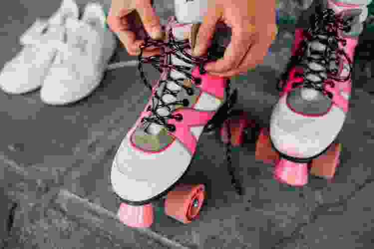 person lacing up a pair of roller skates