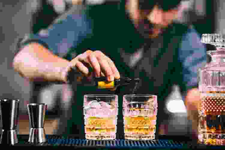 bartender pouring whiskey cocktails