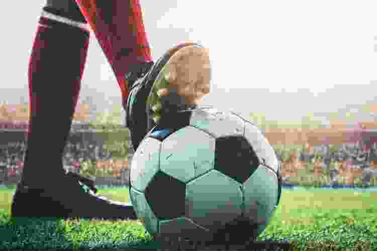 soccer player with their foot on the ball on the soccer field