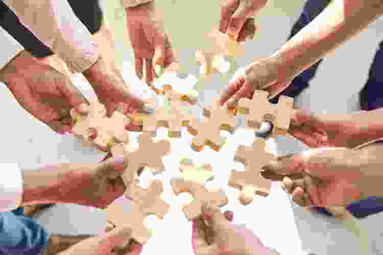 colleagues holding puzzle pieces together