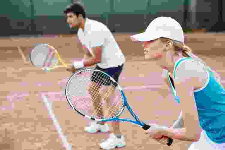 couple playing tennis together on a court
