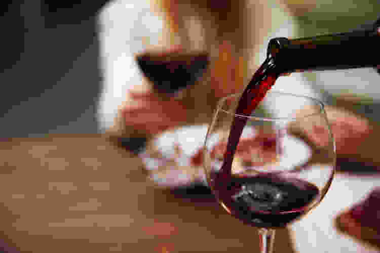 pouring red wine into a glass during dinner