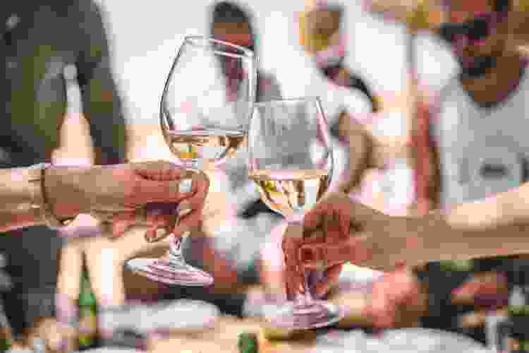 friends enjoying white wine at an outdoor dinner party