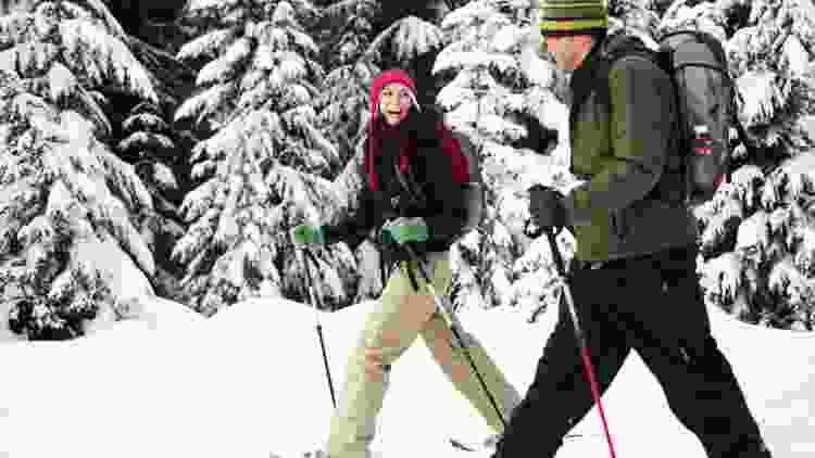 couple snowshoeing through the mountains