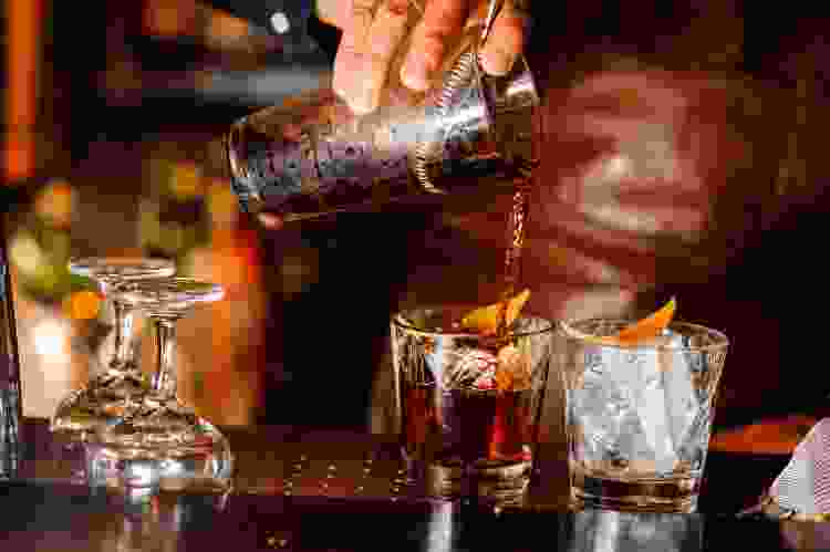 mixologist pouring a whiskey cocktail