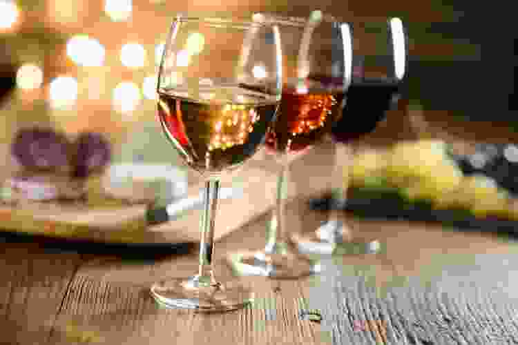three glasses of wine with grapes and charcuterie