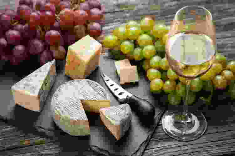 cheese on a slate board with grapes and white wine