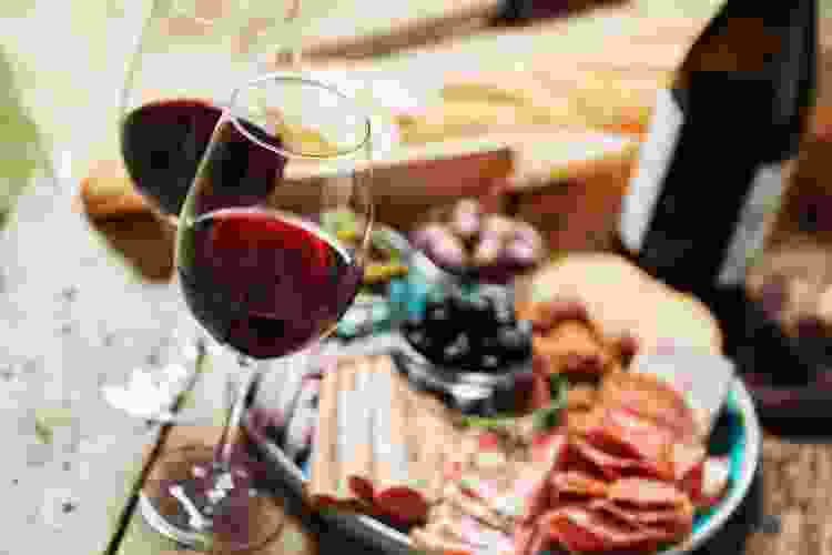 wine glasses with red wine and a charcuterie board