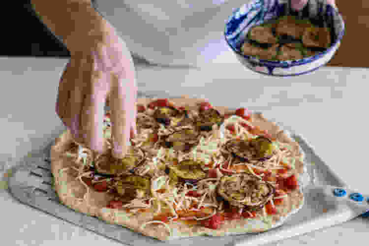 chef topping an eggplant pizza during a cooking class