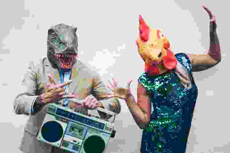 coworkers wearing dinosaur and chicken masks at a themed costume party