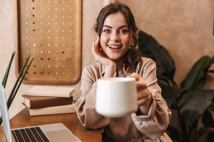 young woman holding a mug of coffee while sitting at a desk