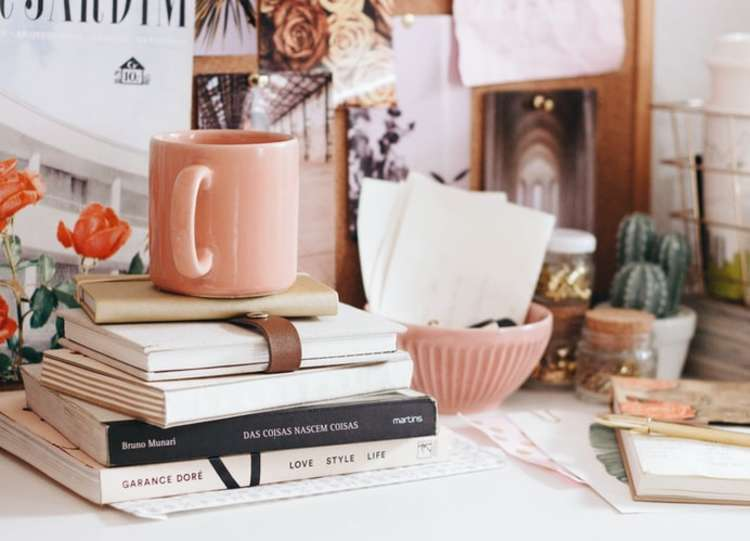 Virtual team building activities: a stack of books on a desk for a virtual book club