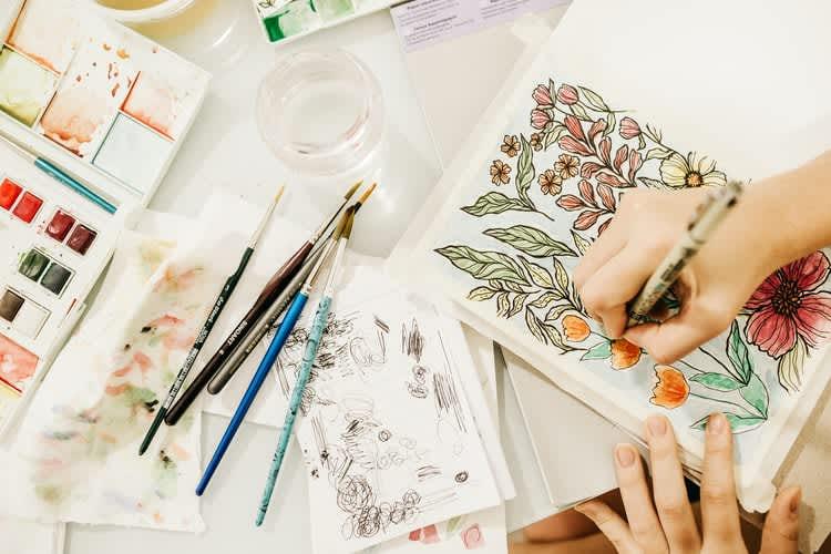 Virtual team building activities: Hands paint in a sketchbook as part of an online art class