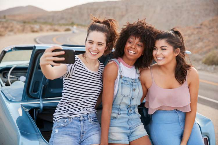 girls taking a selfie while on a road trip