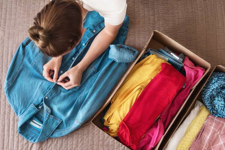 girl folding clothing for a clothes swap