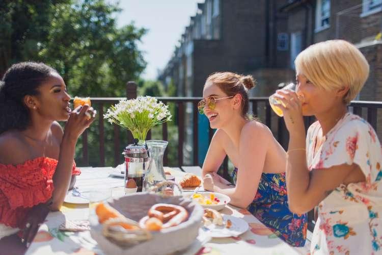 three women chatting over outdoor brunch