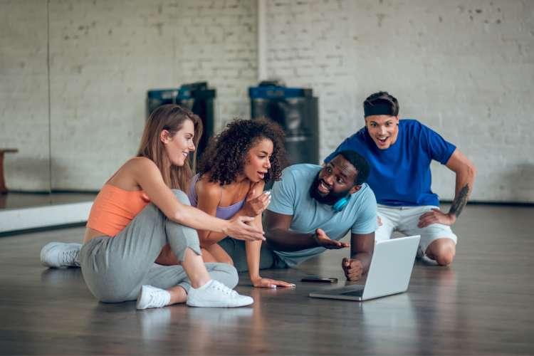 group watching computer in dance studio