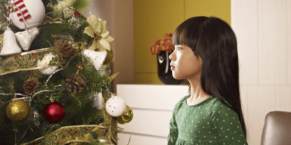 Chinese girl looking at Christmas tree