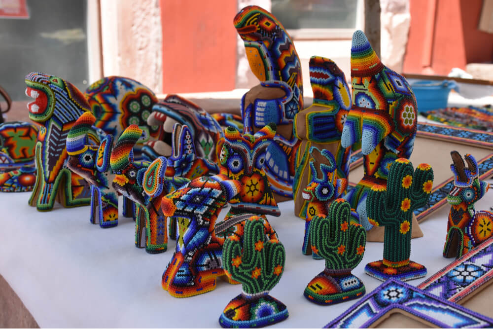 Huichol art includes yarn paintings and symbolic objects decorated with beads