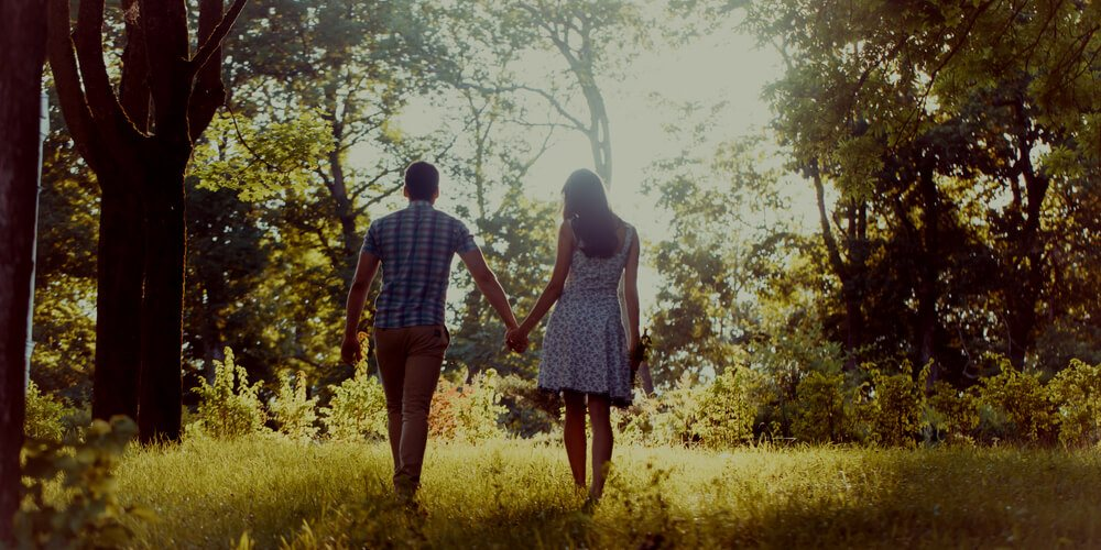 Happy couple walking in a forest