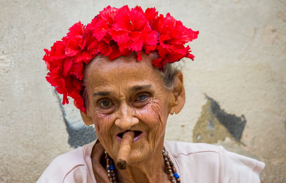 A portrait of an old woman with a cigar sitting on the sidewalk on the street of old Havana, Cuba