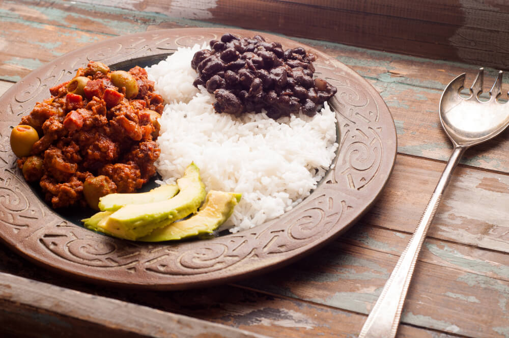 Cuban style beef picadillo served with moros y cristianos (black beans and white rice) and avocado