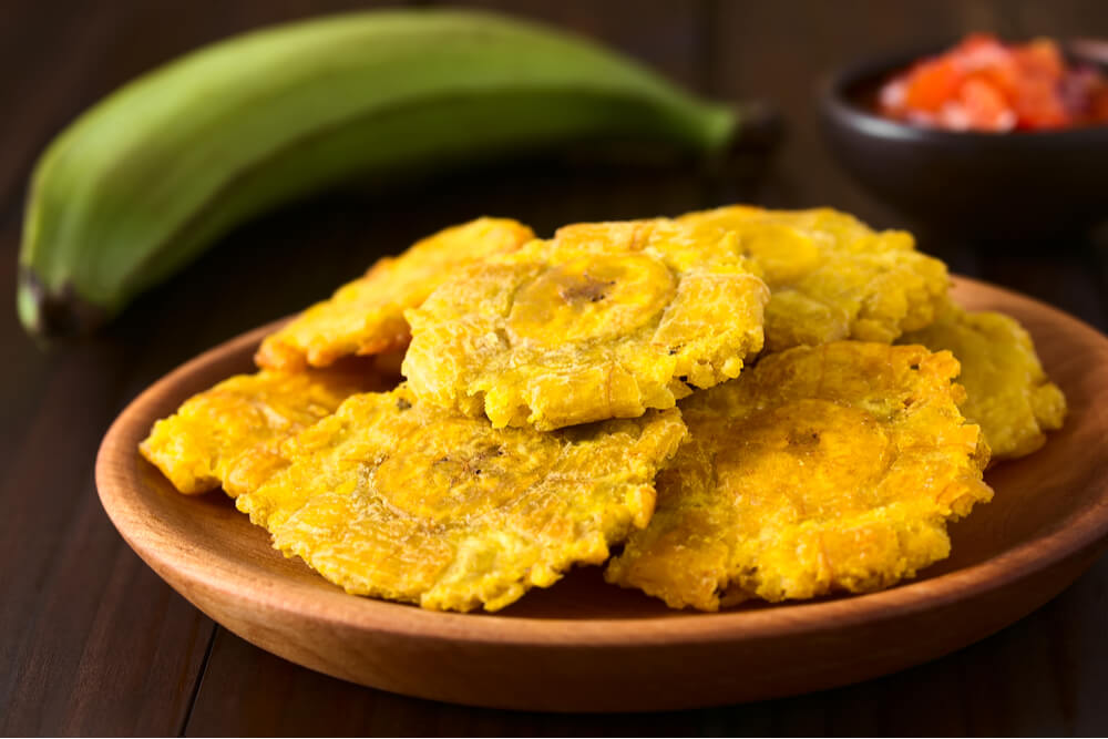 Tostones, fried and flattened pieces of green plantains, are a traditional snack or accompaniment in Cuba