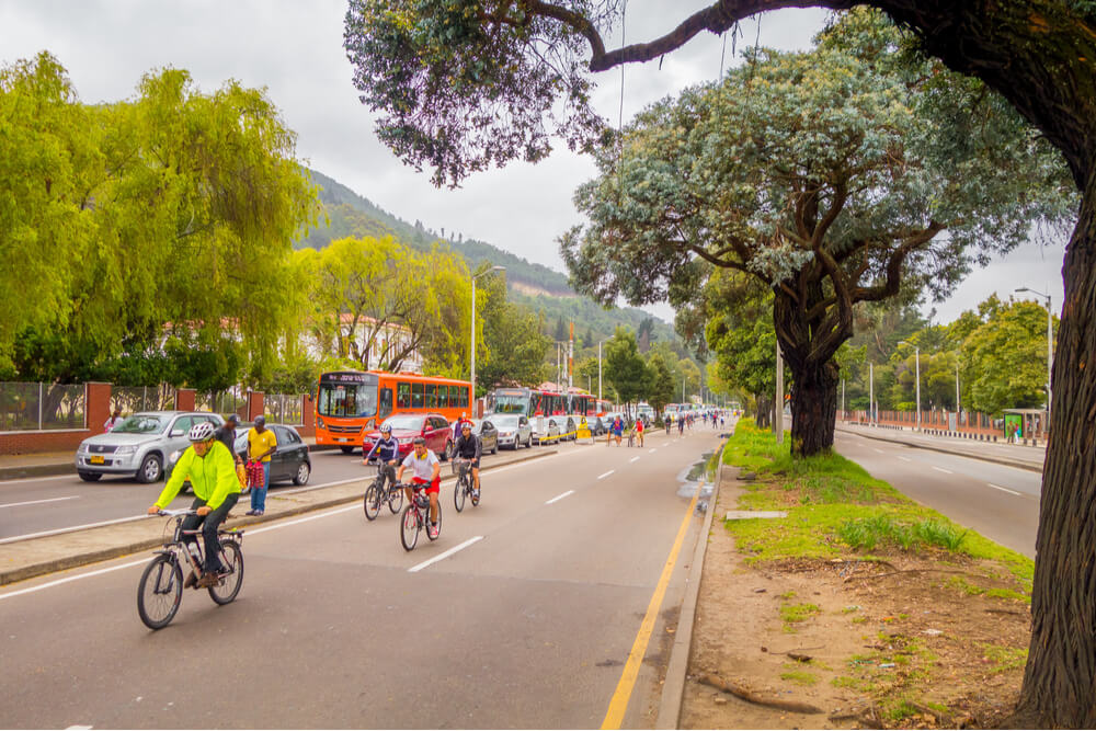 Cyclists moving through a vehicle-free street with heavy traffic in the opposite lane in Candelaria area Bogota, Colombia