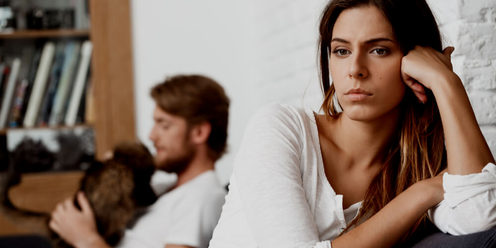 Unhappy woman with a man behind her
