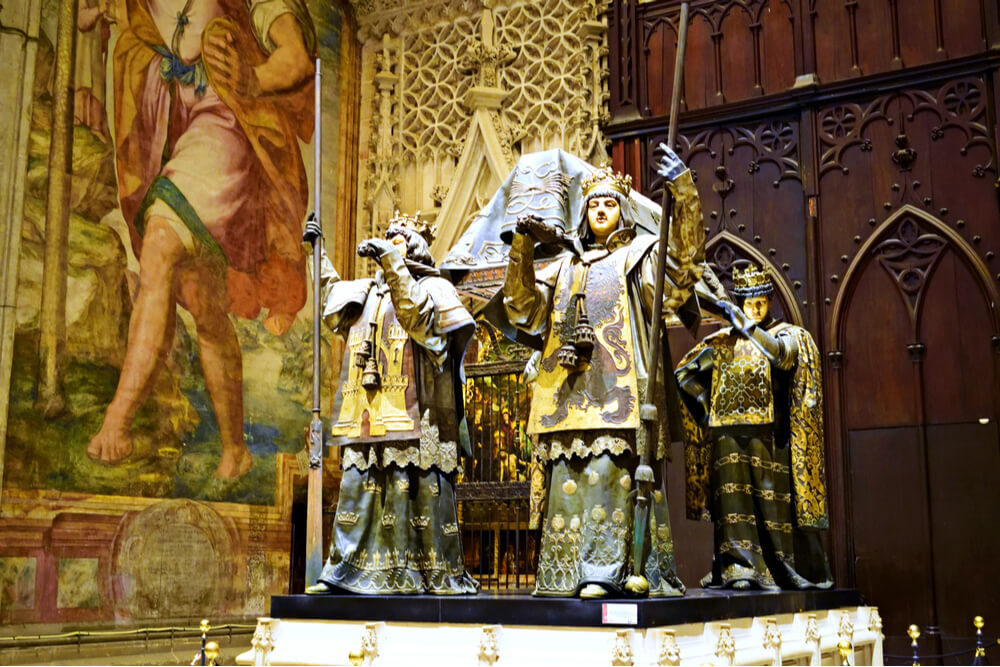 The tomb of Christopher Columbus carried by four heralds representing the four crowns of Spain located inside the Cathedral of Seville