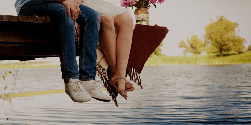 Legs of romantic couple near a lake