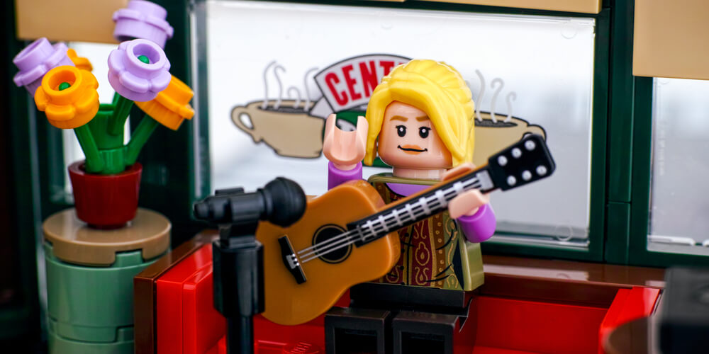 Lego Phoebe Buffay minifigure performing songs on guitar in Central Perk cafe.