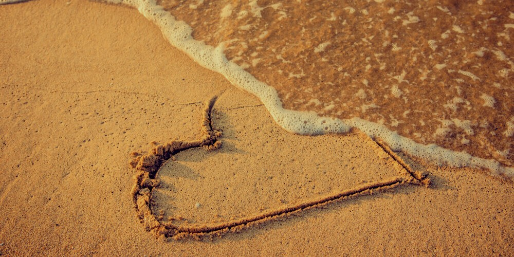 Heart on a beach washed off by a wave
