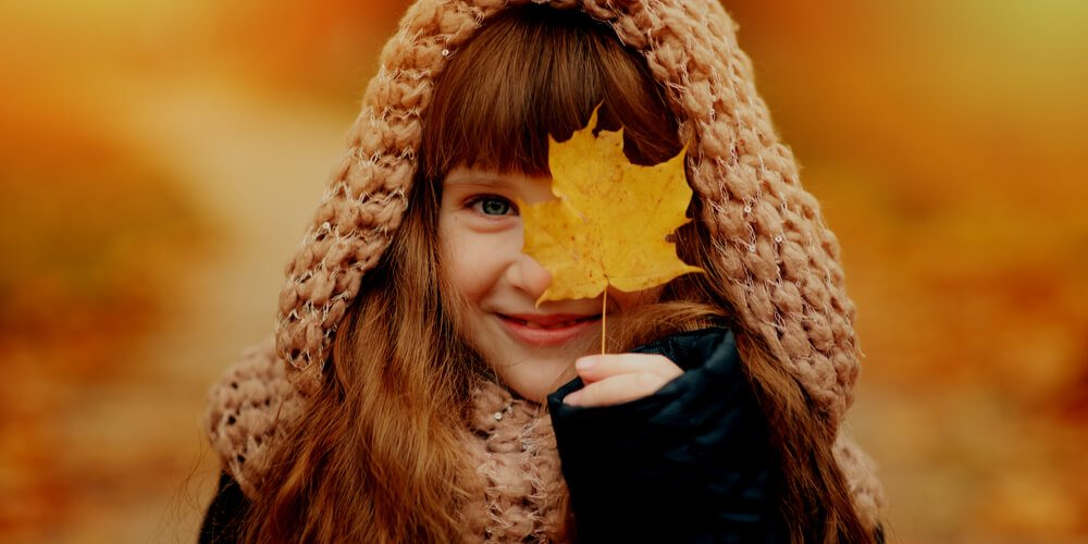 Small girl with an autumn leaf