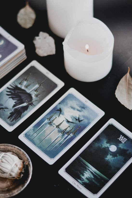 three card tarot spread with white candles