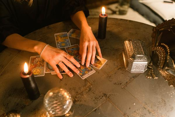 woman spreading tarot cards on table with candles and crystal ball