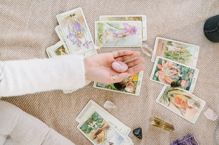 woman holding a crystal with tarot cards behind her hand