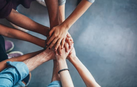 Image is taken from above and is of a group of people who have stacked their hands on top of each other. Disability advocacy communities. Inform online.