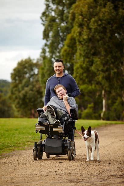 Support worker with man and dog in park