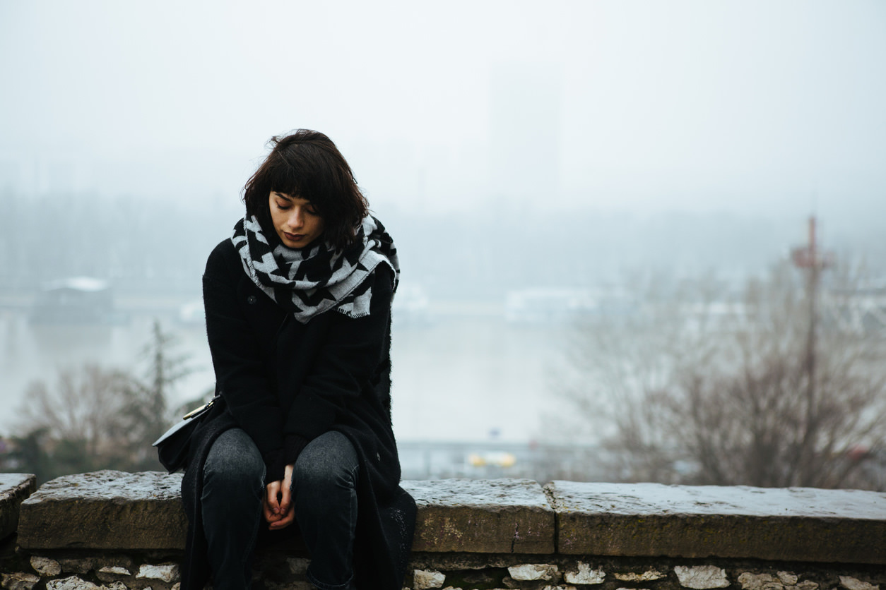 Girl sitting on edge of a stone wall