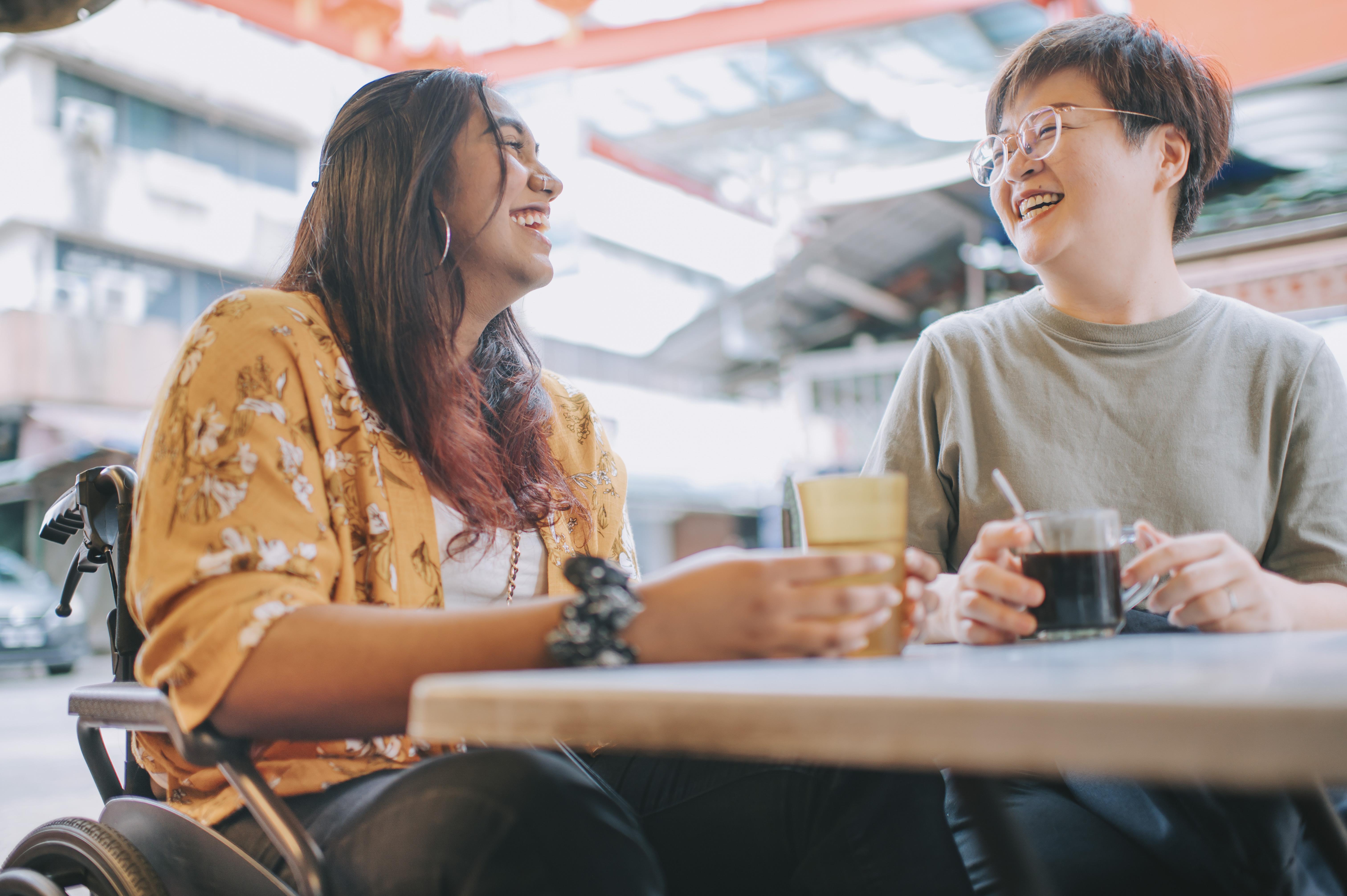 Women in wheelchair having coffee with friend