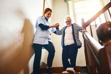 Disability Support Worker Assisting Lady down stairs