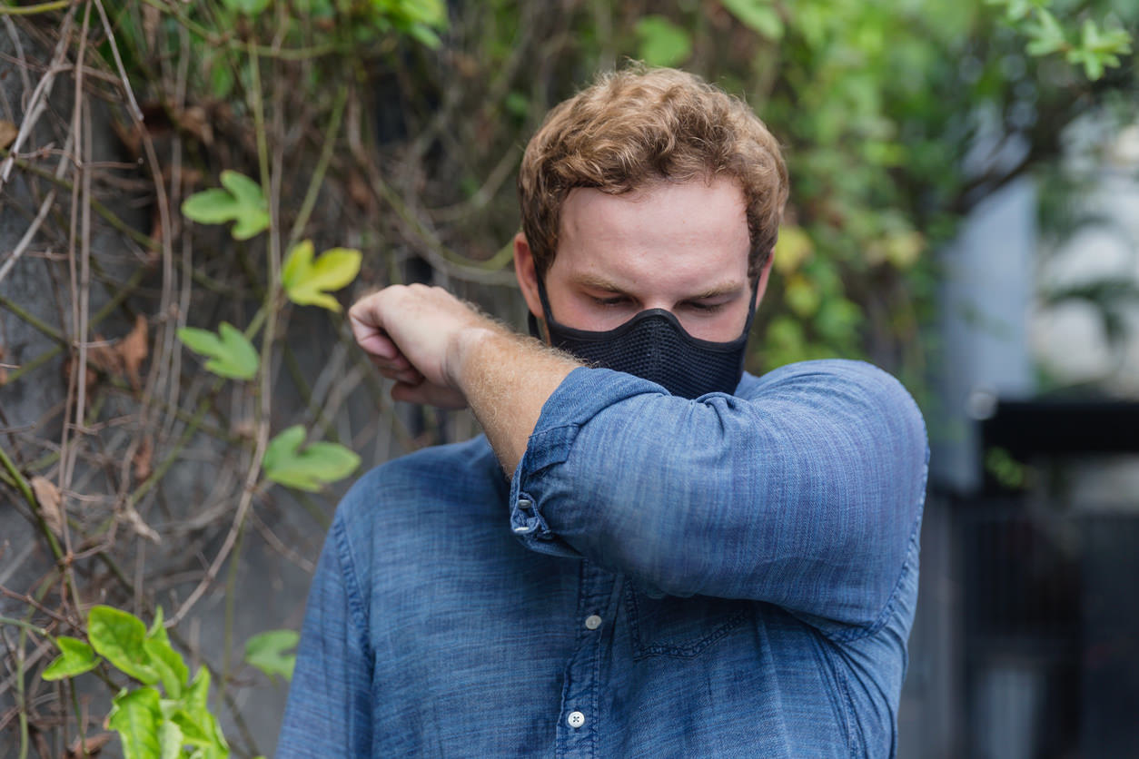 Man with a face mask sneezing into his elbow